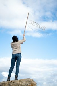 woman flying Jesus banner